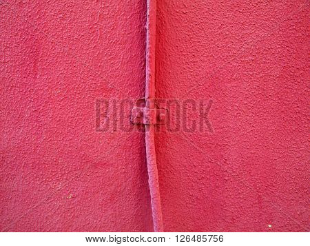 Detail of a pink wall with a thin pipeline crossing it