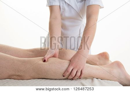 Adult Male Physiotherapist Treating The Leg Of Male Patient.