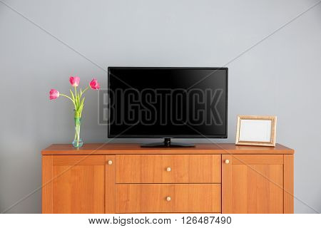 wide screen TV on wooden commode near grey wall