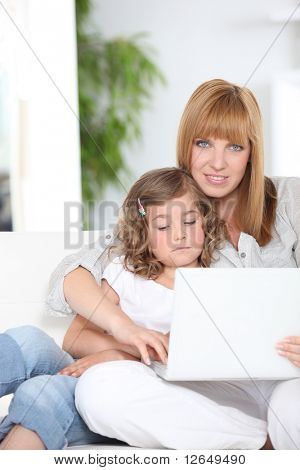 Woman and little girl in front of a laptop computer