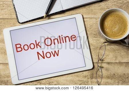 Tablet with Book online now on wooden table