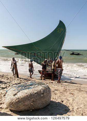 Cumbuco, State of Ceara, Brasil - August 19, 2013: Fishermen are getting ready to enter the sea for fishing with their jangada, the traditional small boat of the Brazilian Northeast