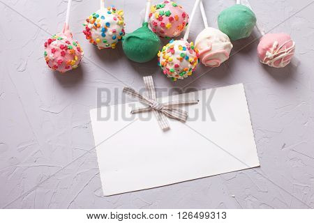 Colorful cake pops and empty tag on grey textured background. Selective focus. Place for text.