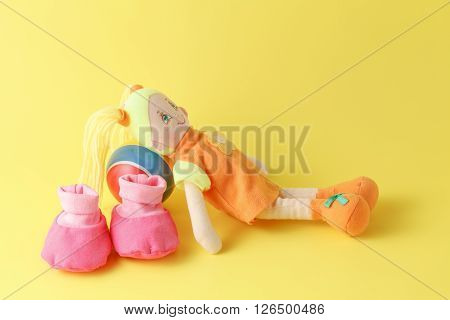 Babby Booties And Dolls On Yellow Background