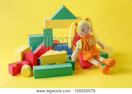 Toy house and doll with blocks on yellow
