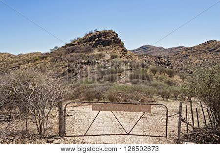 farm gate with warning sign north of Windhoek, Namibia