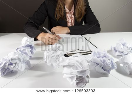 Businesswoman sitting at her desk with mistake resume.