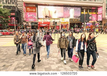 HONG KONG - 22 FEBRUARY 2015: crowd of multiracial people crossing the road on Nathan Street near Tsim Sha Tsui in city heart of Hong Kong; special administrative region of People's Republic of China