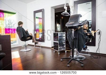 Customers Undergoing Hair Treatment In Beauty Salon