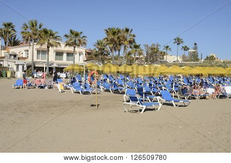 MARBELLA, SPAIN - APRIL 9, 2016: Some people sunbathing on blue sun beds in a day in spring in Marbella Spain.