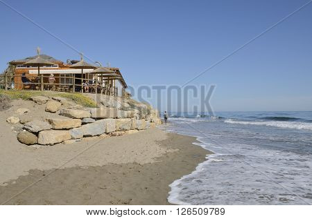 MARBELLA, SPAIN - APRIL 9, 2016: Woman walking at the shore next to a bar over rocks in the beach of Marbella a city in southern Spain belonging to the province of Malaga Andalusia Spain