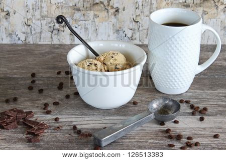 Bowl of coffee ice cream, cup of coffee, coffee beans, chocolate and vintage ice cream scoop