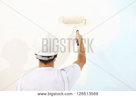 painter man at work with a paint roller wall painting concept poster