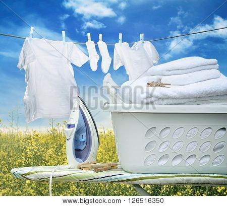 Iron on ironing board with laundry basket