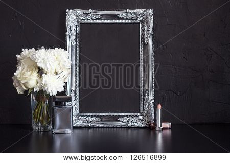Vintage photo frame and flowers on a black textured background.