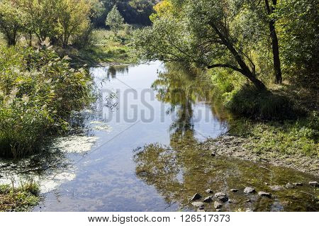 the small still hush river with rusty banks