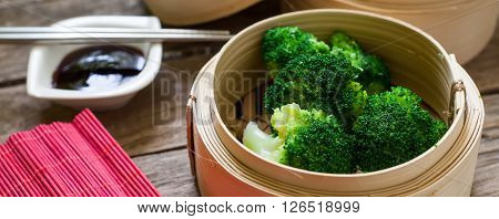 steamed fresh broccoli on bamboo pan with soya sauce for dip