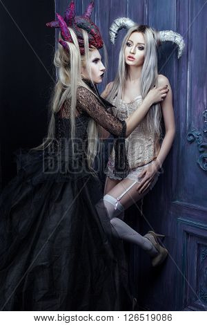Two women in gothic outfits their hair on the head with horns.