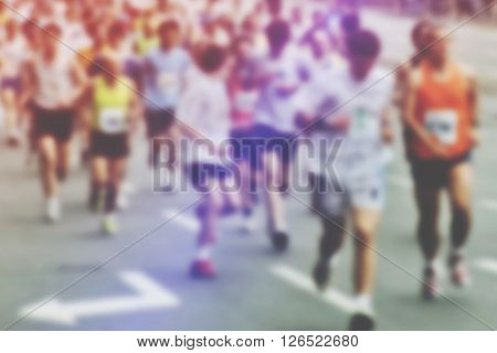 Blur image of people running a marathon race through city defocussed photo of sport event unrecognizable man and women racing through urban environment retro toned