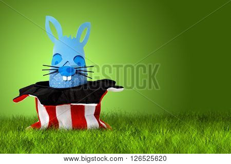 Funny Easter bunny coming out from clown hat on gree background from left side with copy space on the right side.