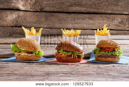 Hamburgers and cups with fries. Table with burgers and fries. Delicious high calorie meal. Taste you will never forget.