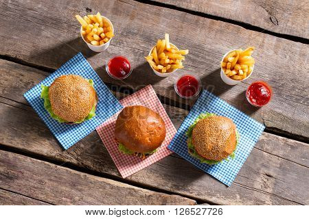 Fries with ketchup and burgers. Burger menu on wooden table. Bright colors of satiety. Just have a bite.