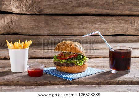 Hamburger with fries and cola. Burger and drink on table. Wooden table in retro diner. Tasty junk food in bistro.