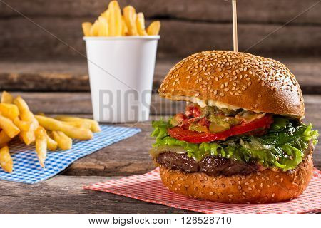 French fries and big burger. Junk food on brown table. Well made burger in cafe. Example of popular junk food.