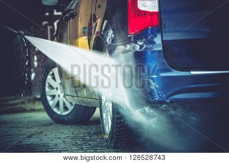 Backyard Car Washing Closeup Photo. Power Washing and Cleaning Family Van.