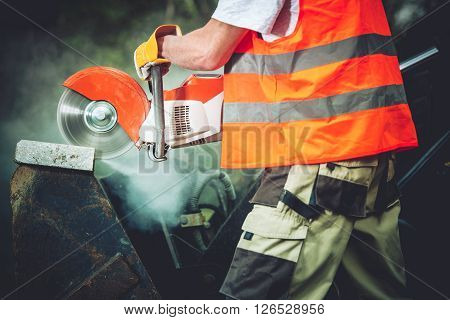 Concrete Cutting Construction Power Tool Closeup Photo. Construction Worker Cutting Concrete Block Using Electric Cutter.