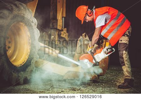 Construction Worker in Action. Worker Cutting Concrete by Using Heavy Duty Electric Cutter. Construction Site.