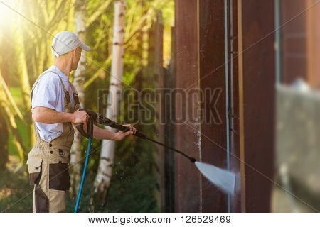 Garage Gate Water Cleaning. Garage Walls and Gate Powerful high Pressure Water Washing. Caucasian Worker Cleaning Building Elements.