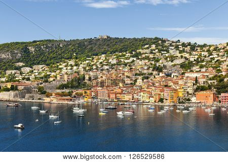 Coast view of picturesque French Riviera town Villefranche-sur-Mer with leisure boats anchored in harbor, citadel and fort Mont Alban on hill.