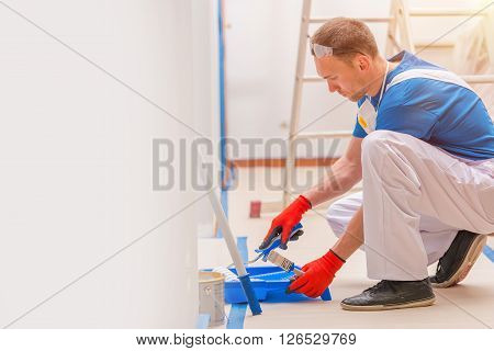 House Walls Painting. Young Caucasian Men Painting His Home. Construction and Renovation.