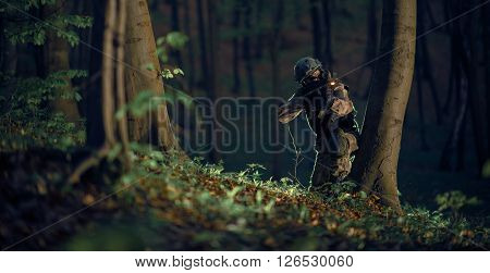 Military Soldier in Action at Night in the Forest Area. Night Time Military Mission. Panoramic Photo. Soldier with Assault Rifle with Flashlight Between Trees.