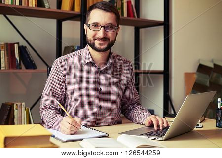 Close up of smiling young businessman with the glasses who rewriting from his laptop