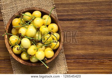 Ripe yellow or Rainier cherry in wooden bowl photographed overhead on wood with natural light (Selective Focus Focus on the top cherries)