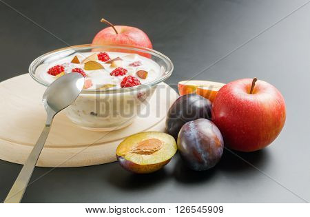 Glass bowl filled with yogurt mixed with fruit pieces arranged on wooden board with spoon and some apples and plums around on neutral background.