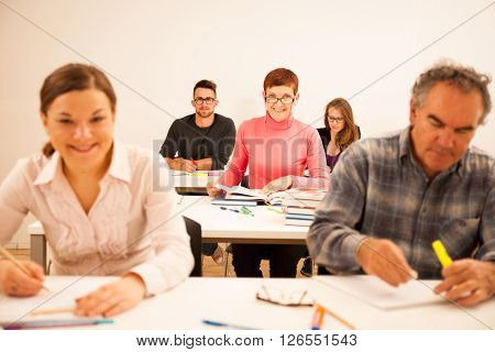 Group of people of different age sitting in classroom and attending a school for adults. Lifelong learning.