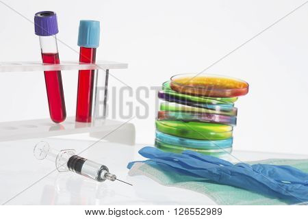Biochemistry Research of blood tests. Cell culture for the biomedical diagnostic. Gloves,  petri dish for blood analysis,  Plastic labware for scientific research and personal protection equipment.