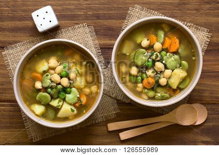 Vegetarian chickpea soup with carrot broad bean (fava bean) pea potato onion garlic and parsley served in bowls photographed overhead on wood with natural light