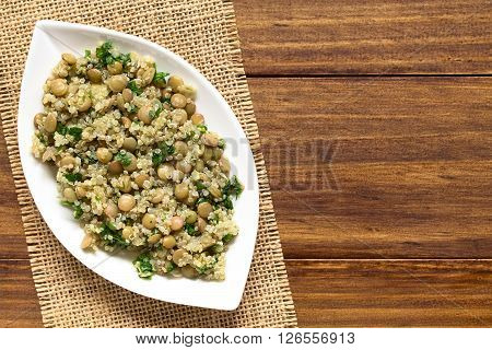 Quinoa salad with lentils and parsley on plate photographed overhead on wood with natural light