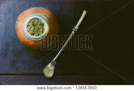 Yerba herb mate in calabash on black background. Top view