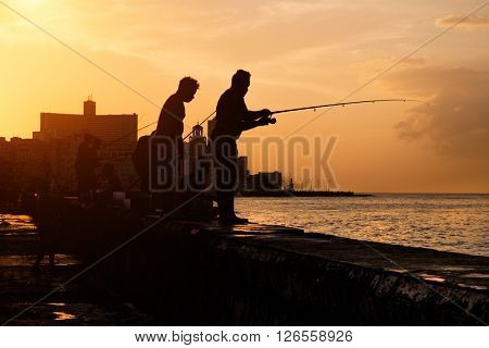 Beautiful sunset in Havana with the silhouette of group of fishermen on the Malecon seawall