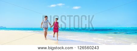 Panorama summer vacation couple walking on beach. Young adults having fun together enjoying their holidays travel in perfect getaway in sunny tropical destination with pristine turquoise ocean water.