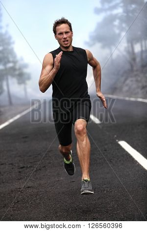 Running runner man sprinting workout on mountain road. Jogging male fitness model working out training for marathon on forest road in amazing nature landscape.