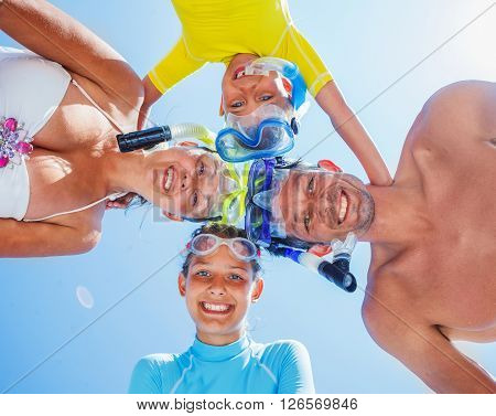 Photo of happy family of divers looking at camera against blue sky during summer vacation
