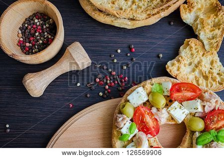 Italian appetizer Friselle. Italian dried bread Friselle with tomatoes cherry, cheese mozzarella, olives, tuna, basil and pepper in wooden pounder. Italian food. Healthy vegetarian food. Top view.