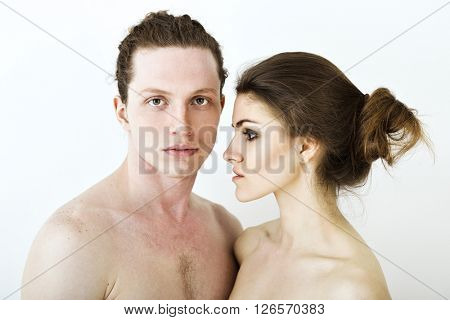Portrait of young contented couple. Young man and woman embracing each other, studio shot. Psychology of relations, heterosexual couple, intimate family questions, sex life concept.