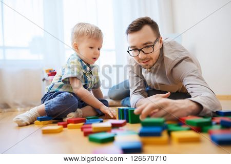 family, childhood, creativity, activity and people concept - happy father and little son playing with toy blocks at home poster